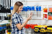 Side view of female customer checking information of screwdriver on mobilephone in hardware store