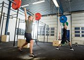 Full length young male athletes exercising with barbells in cross training box