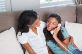 Happy mother and daughter on the phone together on sofa at home in living room