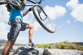 Fit man walking up rocky terrain holding mountain bike on a sunny day