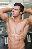 Shirtless muscular man looking away in gym