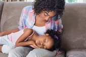 Cute daughter sleeping across mothers lap on the sofa at home in the living room
