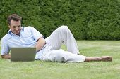 Full length of young man using laptop while lying on grass in park