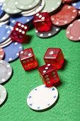 casino chips and dices stacking on a green felt