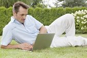 Handsome young man using laptop in park