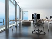 stock photo of workstation  - Modern waterfront office overlooking the sea with several computer workstations on movable wheeled office tables in a bright airy room with a glass view window or wall - JPG