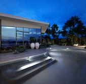 Contemporary luxury house with a glass facade and illuminated curving swimming pool at night with po