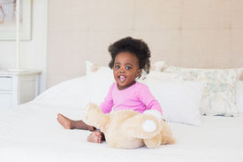 foto of babygro  - Baby girl in pink babygro sitting on bed at home in the bedroom - JPG