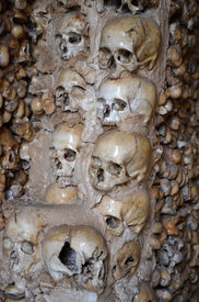 stock photo of skull cross bones  - Human skulls and bones lining a chapel in Portugal