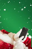 Santa using smartphone against green