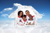Smiling family holding a soccer ball against bright blue sky with clouds