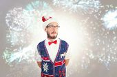 Geeky hipster in santa hat against colourful fireworks exploding on black background