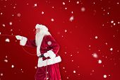 Santa pulls something with a rope against red background