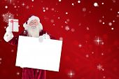 Santa shows a present while holding sign against red snowflake background