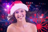 Close up portrait of pretty woman in santa hat against digitally generated nightclub under lights
