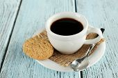 Cup of coffee with burlap cloth, spoon and cookies on color wooden background