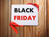 Card with Black Friday text on wooden background