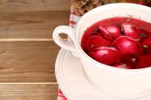 Traditional polish clear red borscht with dumplings on wooden background