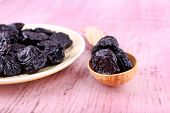 Bowl and spoon of prunes on color wooden background