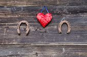 Two Luck Symbols Rusty Horsehoe And Red Cloth Heart On Wall