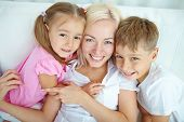 Happy young woman and two children looking at camera