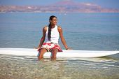 Young sporty man sitting on surfboard in low water