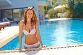 Happy young woman swimming in pool at resort