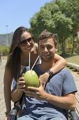 handicapped man in wheelchair and girlfriend drinking coconut water