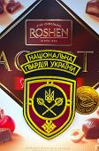 Kiev,Ukraine.Dec 20.Illustrative editorial.Chevron of Ukrainian National Guard.With logo Roshen Inc. Trademark Roshen is property of ukrainian president Poroshenko.At December 20,2014 in Kiev, Ukraine