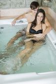Young Couple Relaxing In The Hot Tub
