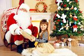 Santa Claus giving  present to  little cute girl near Christmas tree at home
