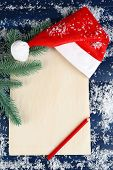 Santa red hat with branch of fir-tree, sheet of paper, pencil and snowflakes on color wooden background