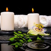 Spa Setting Of Passiflora Flower, Green Branch Fern, Towels And Candles On Zen Stones In Ripple Refl
