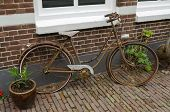 Old rusty bike against a property in the Netherlands