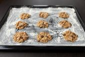 pic of baked raisin cookies  - uncooked oatmeal cookies with raisins on baking tray - JPG