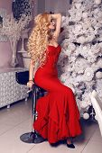 Woman With Blond Hair In Luxurious Red Dress Posing Beside A Christmas Tree