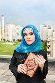 stock photo of hijabs  - beautiful muslim woman wearing hijab and holding holy book Koran