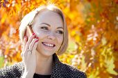 Portrait of young woman talking on mobile phone in autumn park
