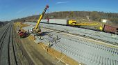 stock photo of construction crane  - Construction crane with sleepers and workers at construction of new railway lines - JPG