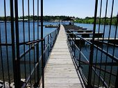 stock photo of dock a lake  - A beautiful wrought iron gate leading to a wooden dock on a lake for boats and fishing - JPG