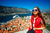 pic of vest  - Young woman traveler in red vest with backpack on the Lovcen mountain near the old city Kotor - JPG