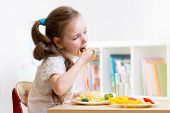 stock photo of healthy eating girl  - preschooler kid girl eating healthy food at home or kindergarten - JPG