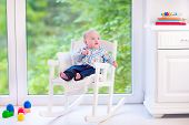 picture of daycare  - Cute funny baby adorable little boy wearing a colorful shirt relaxing in a white rocking chair next to a big garden view window at home or daycare center
