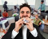 pic of stress-ball  - Young angry businessman while eating balled paper in office. ** Note: Shallow depth of field - JPG