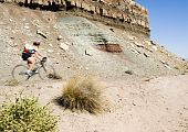 stock photo of semi-arid  - A biker rides through the scenery along the Rim Rock Drive in Colorado National Park - JPG