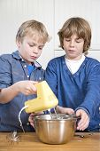 pic of cake-mixer  - Two friends mixing dough in a stainless steel bowl using a mixer - JPG