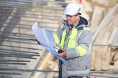 stock photo of inspection  - Civil Engineer at construction site is inspecting ongoing production according to design drawings - JPG