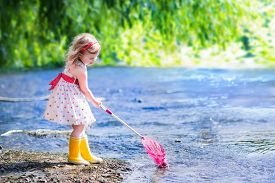stock photo of cute frog  - Child playing in a river - JPG