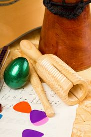 pic of bongo  - Vertical photo of wooden guiro and green egg shaker on piece of paper with written - JPG