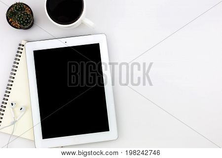 poster of Modern white office desk top table with tablet a cup of coffee notebook and other supplies. Top view with copy space on white background. Top view flat lay.